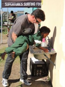 Zack assisting a child with  washing hands.